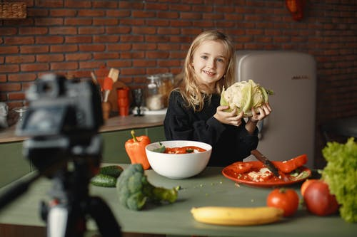 Girl in the Kitchen Holding a Cabbage