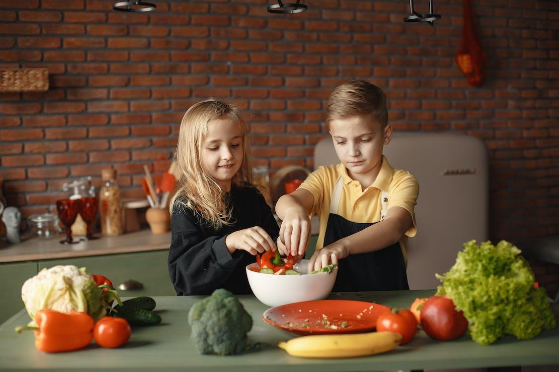 Little friends preparing vegetable salad together in kitchen at home