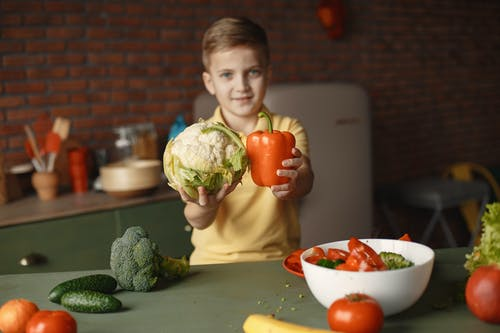 Little child demonstrating fresh red pepper and cauliflower and looking at camera while standing near table with vegetables and ingredients put into deep ceramic salad bowl in kitchen