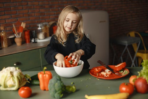 Little girl putting fresh pepper slices into salad bowl