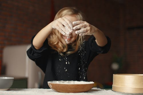 Girl in Black Sweatshirt Sifting Flour