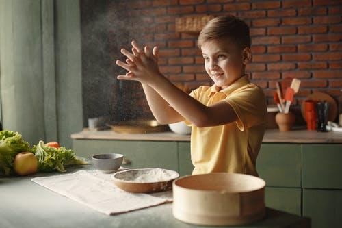 Boy in Yellow Shirt Sifting Flour