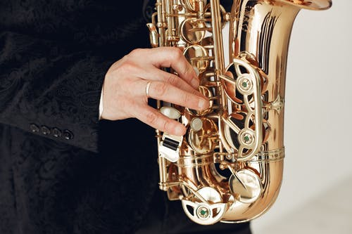 Person Holding Brass Saxophone on Black Textile