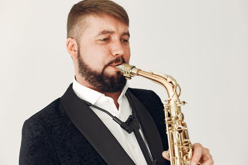 Man in Black Suit Jacket Playing Saxophone