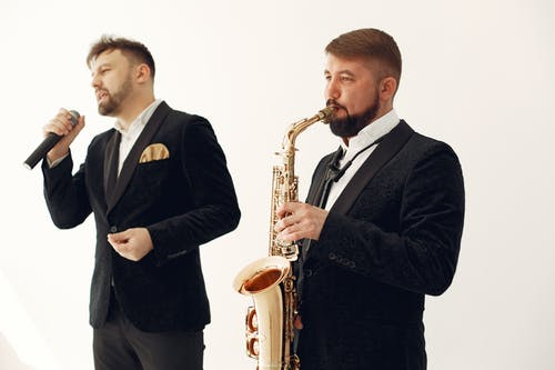Adult male artists wearing elegant concert costumes with saxophone and microphone