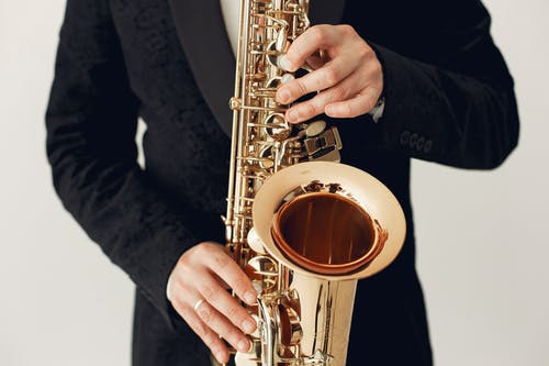 Person in Black Jacket Holding Saxophone