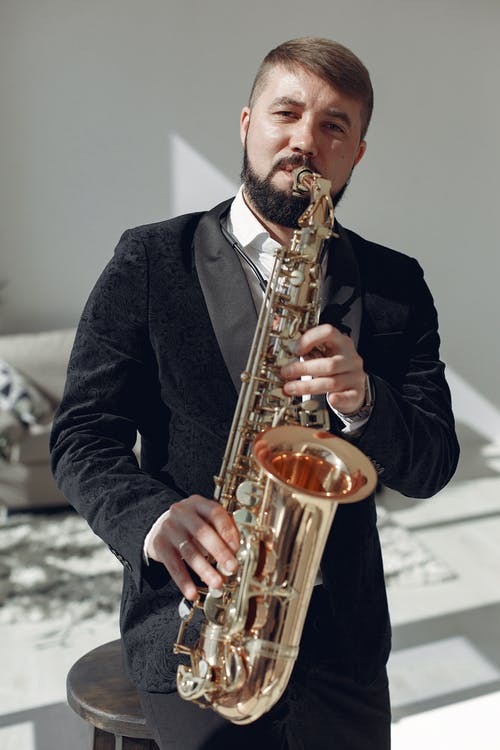 Adult man playing saxophone on concert