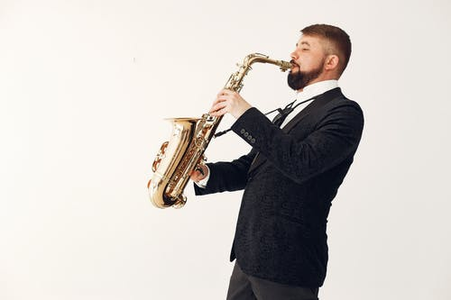 Adult man playing saxophone during rehearsal isolated on white background