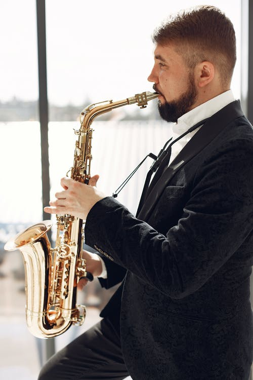 Adult man playing saxophone on event with inspiration
