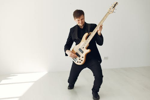 Man in Black Suit Playing Electric Guitar