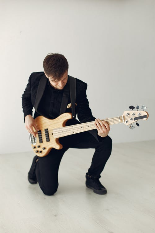 Man in Black Suit Playing White Electric Guitar