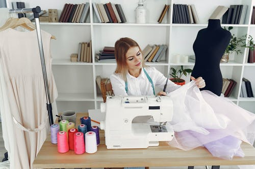 Woman in White Blouse Sitting on Chair in Front of Sewing Machine