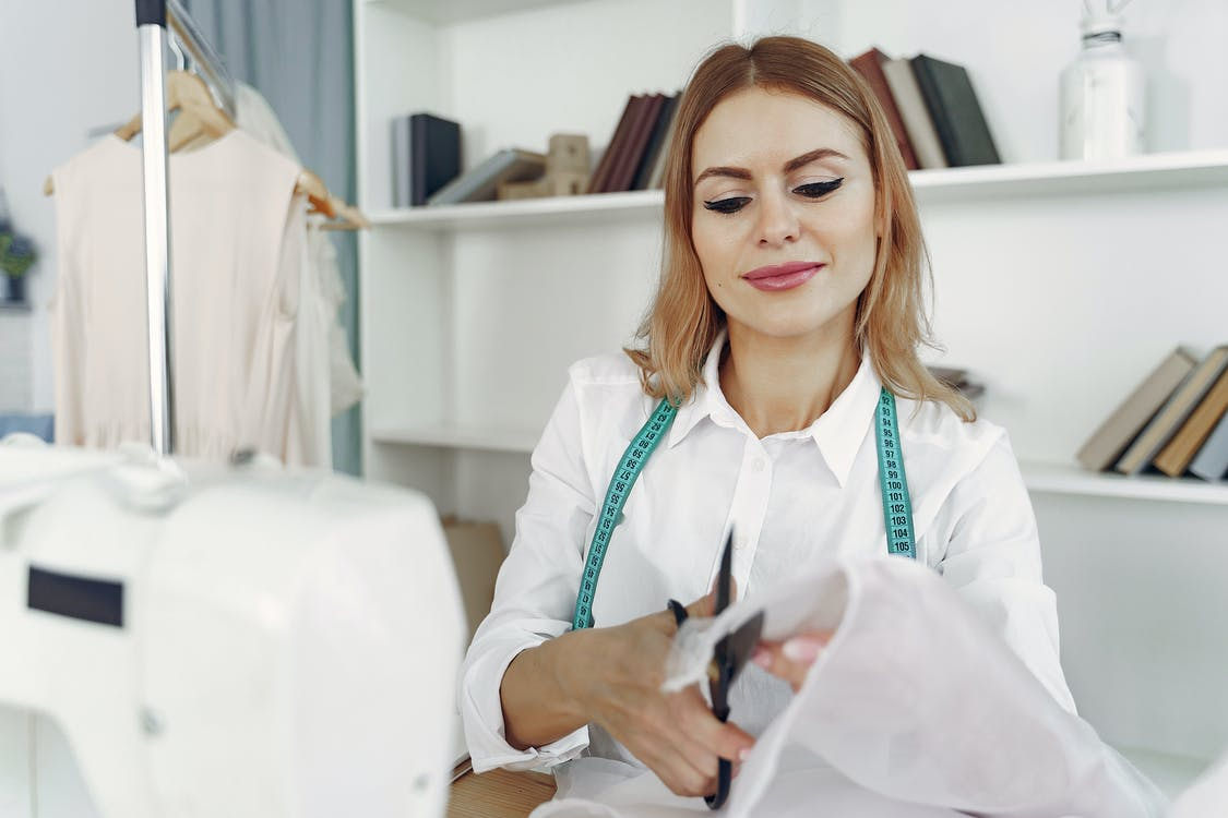 Dressmaker in front of her Sewing Machine Cutting Fabric