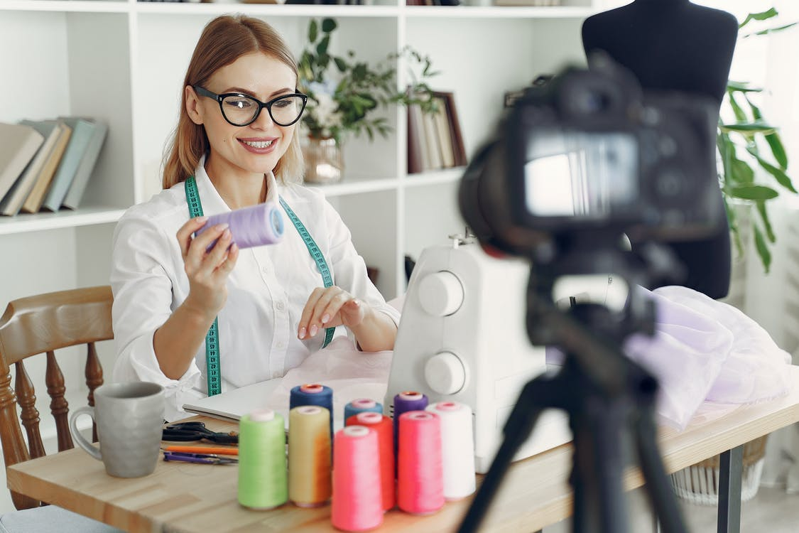 Dressmaker in front of her Sewing Machine and Camera