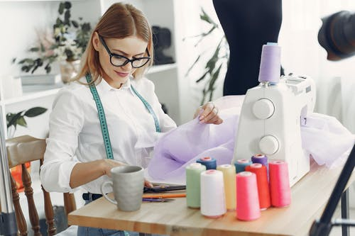 Woman in White Long Sleeve Shirt Wearing Black Framed Eyeglasses in Front of Her Sewing Machine