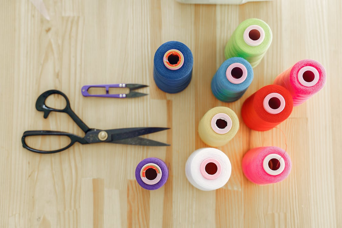 Black Handled Scissors Beside Colorful Threads