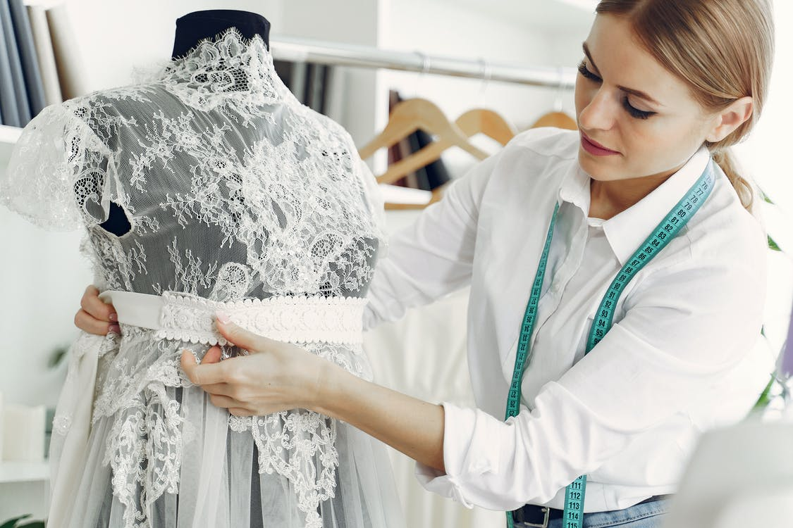 Talented female tailor wearing white shirt and jeans working with mannequin in modern atelier or wedding boutique while attaching belt on lace dress