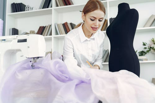 Young inspired seamstress sewing party dress in tailor atelier