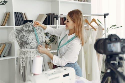 Cheerful female dressmaker creating lace dress in workshop