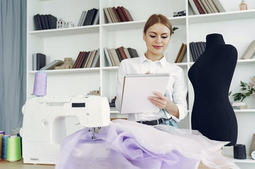 Young positive female dressmaker creating party dress in tailor atelier