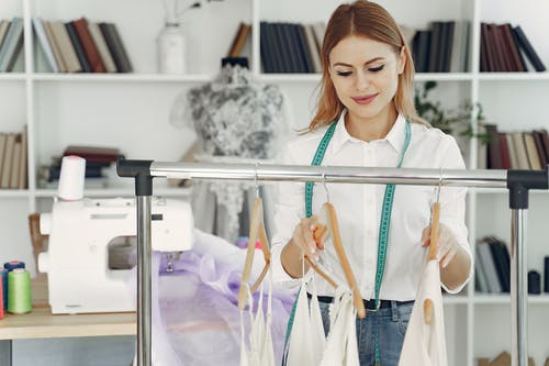 Woman in White Button Up Shirt Hanging Clothes on the Rack