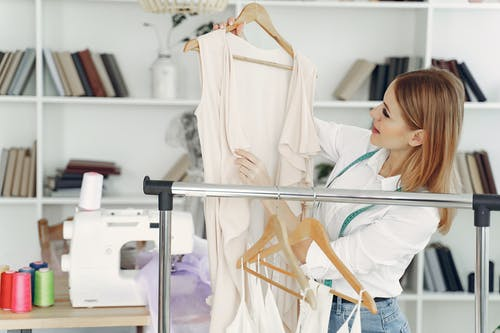 Woman in White Long Sleeve Shirt Holding White Clothes Hanger