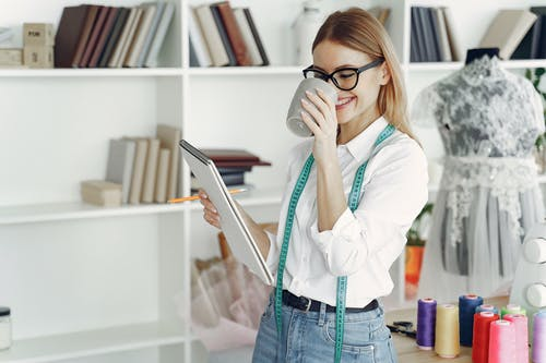 Woman in White Dress Shirt and Blue Denim Jeans Holding Sketchpad and Drinking Coffee