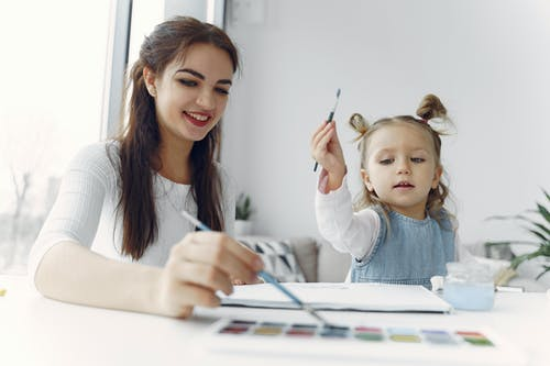 Woman in White Long Sleeve Shirt Holding Paint Brush Beside a Child in Blue Denim Dress Jacket