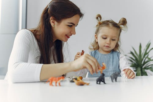 Adorable little girl sitting at white table with mother while playing with small toy wild animals for early education and development during spending time together at home