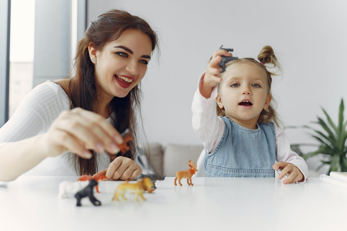 Little Girl Playing Animal Figures with Her Mother