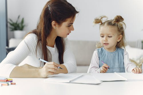 Woman Teaching Little Kid How To Draw