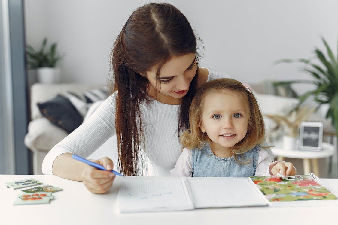 Woman in White Long Sleeve Shirt Holding Girl in White Shirt Writing on White Paper