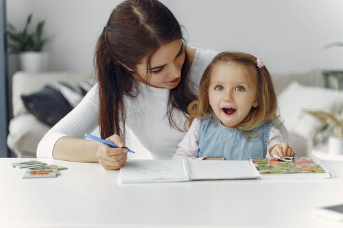 Woman Teaching Little Girl How To Write