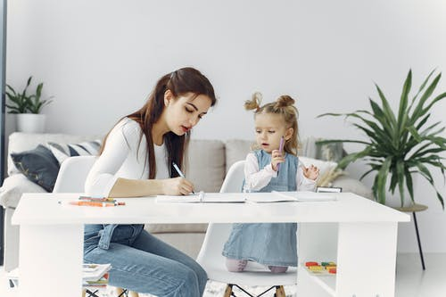 Woman in White Long Sleeve Shirt Sitting Beside Girl Writing on the Notebook