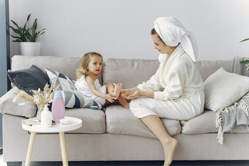 Woman in White Robe Sitting on Couch with Her Daughter
