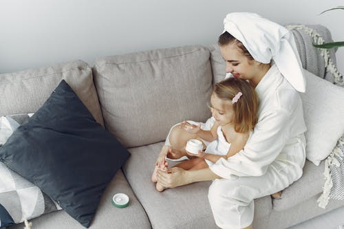Woman in White Robe Sitting on Gray Couch with Her Little Girl