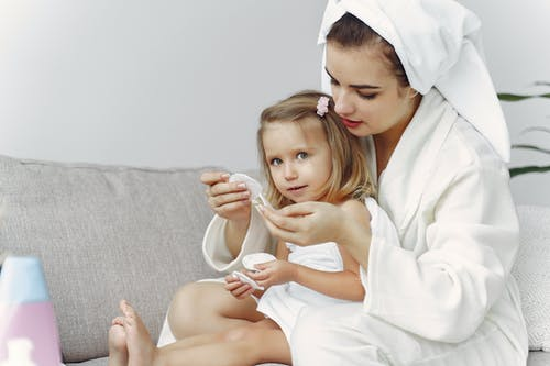 Woman in White Robe Hugging Girl Covered in White Towel