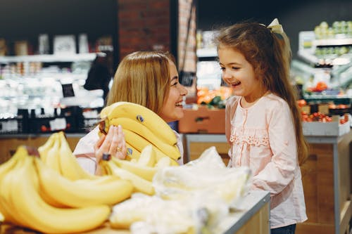 Mother And Daughter Buying Bananas