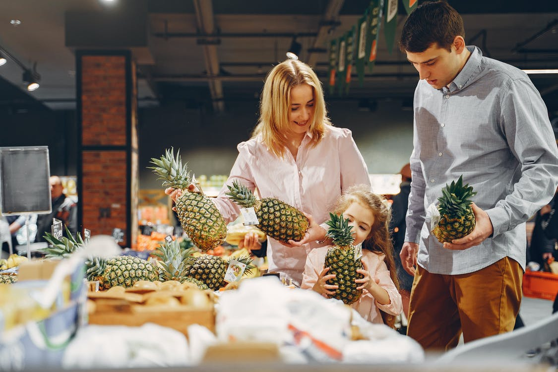Family Buying Fresh Pineapples