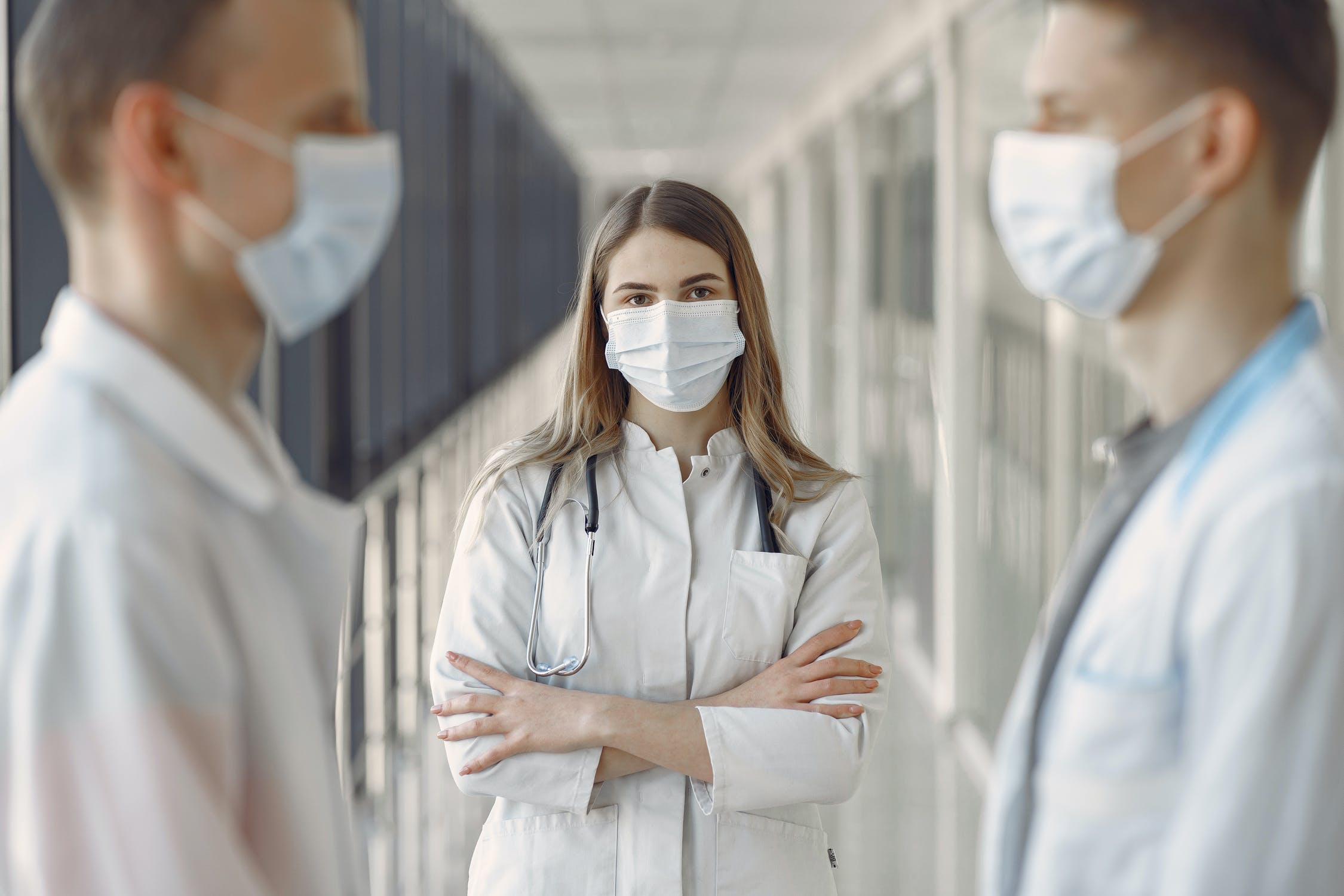 Three people in lab coats wearing face masks talking. Photo by pexels user Gustavo Fring. Photo used courtesy of Pexels.com.