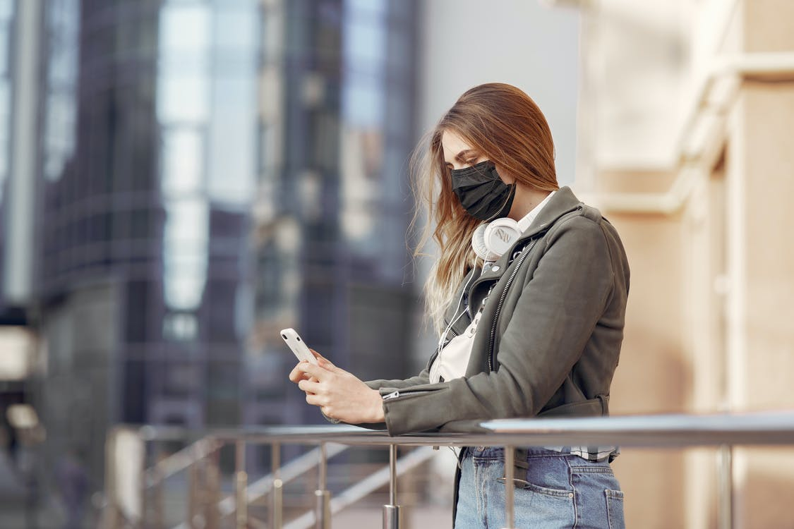 Woman in Gray Coat Holding Smartphone