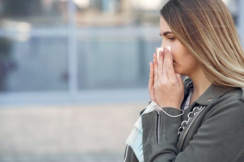 Woman in Gray Jacket Covering Her Nose