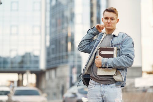 Man in Blue Denim Jacket Holding Books