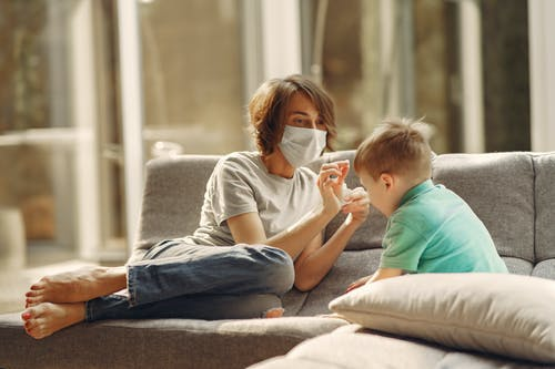 Woman with Face Mask Playing with Her Son
