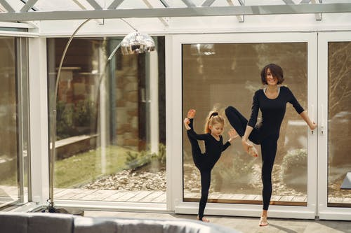 Mother and Daughter Doing One Leg Stand