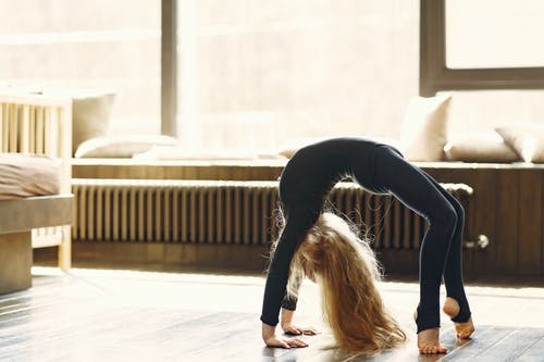 Flexible unrecognizable female gymnast standing in bridge pose on parquet