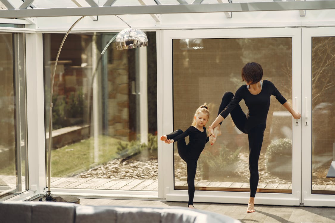 Young barefoot gymnast training with unrecognizable mother at home