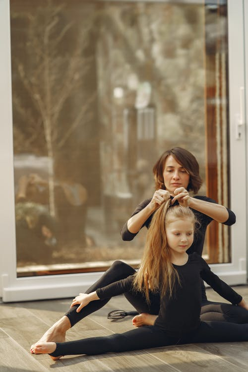 Little Girl Doing Split while Her Mom Fixing Her Hair