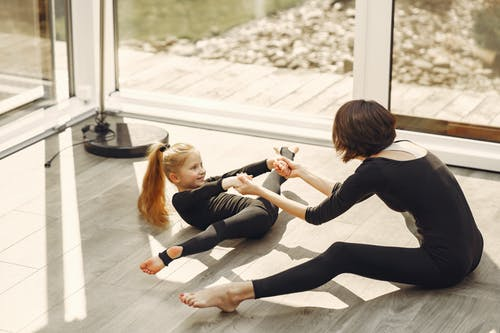 Woman and Little Girl in Black Long Sleeve Shirt and Black Leggings Doing Split