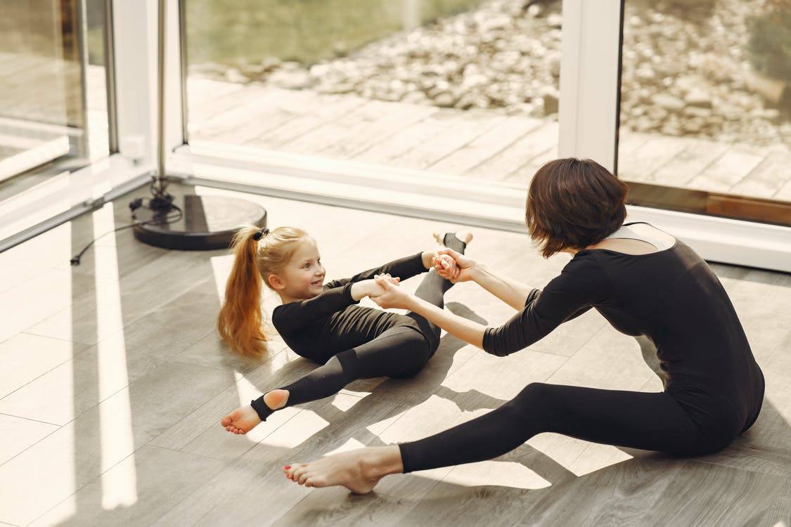 Woman and Little Girl in Black Long Sleeve Shirt and Black Leggings Doing Split